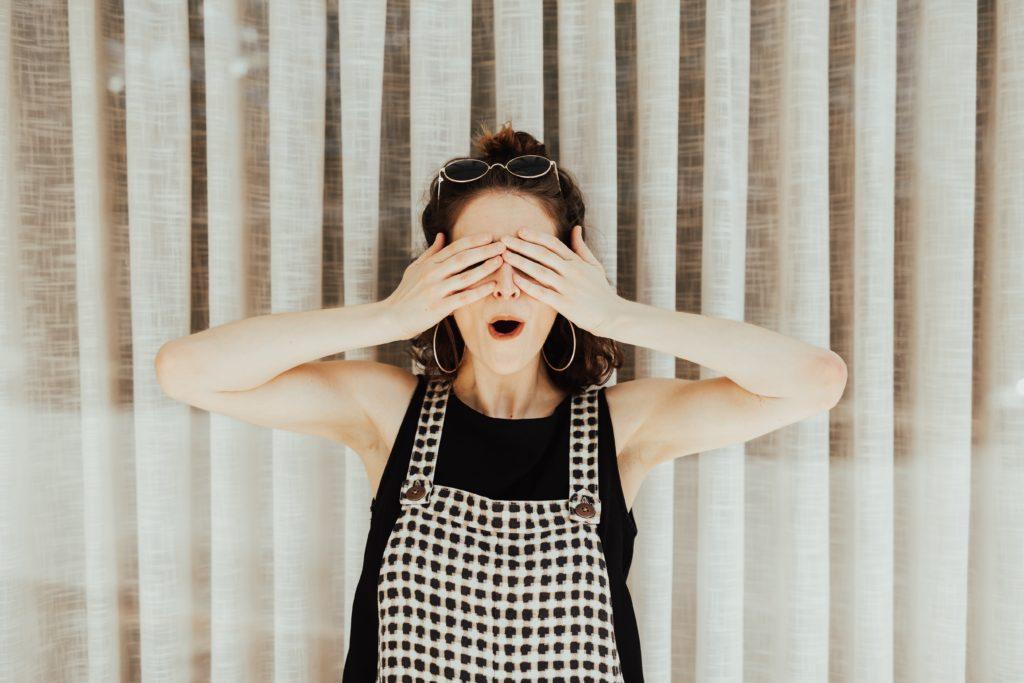 nainen peittää silmät käsillään ja on yllättyneen näköinen