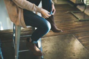 nainen istuu penkillä ja pukee päälleen, kuva: Chelsea Francis, Unsplash