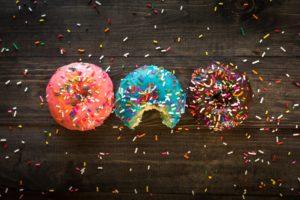 kolme donitsia rinnakkain, joista keskimmäisestä on haukattu pala, kuva: Patrick Fore, Unsplash