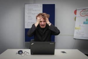 mies repii hiuksia päästään tietokoneen ääressä, kuva: Sebastian Herrmann, Unsplash
